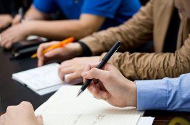 Kennisgemeenschap Hulpmiddelenzorg - Man schrijft met pen aantekeningen in een schrift